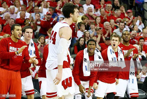 The Wisconsin Badgers bench cheers for Frank Kaminsky of the Wisconsin Badgers in the second half against the Coastal Carolina Chanticleers during...