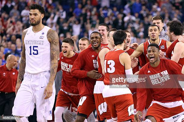 The Wisconsin Badgers celebrate after defeating the Kentucky Wildcats as Willie CauleyStein looks on during the NCAA Men's Final Four Semifinal at...