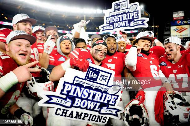 The Wisconsin Badgers celebrate after the Badgers won the New Era Pinstripe Bowl 353 against the Miami Hurricanes at Yankee Stadium on December 27...