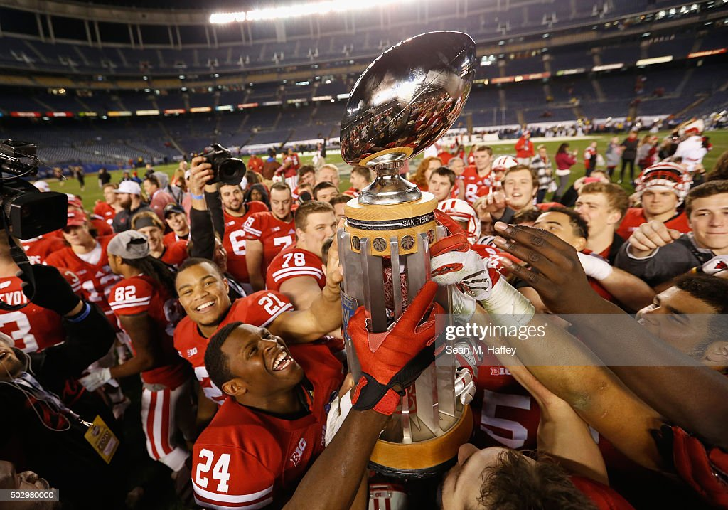 The Wisconsin Badgers celebrate with a trophy after a game against the USC Trojans at the National University Holiday Bowl at Qualcomm Stadium on December 30, 2015 in San Diego, California. The Wisconsin Badgers defeated the USC Trojans 23-21,
