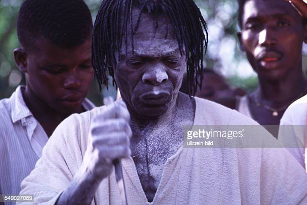 The witchdoctor clothed in a white smock and covered with white kaolin stabs a knife in the air and throws white kaolin on the path The symbolical...