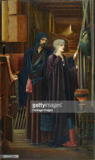 The Wizard, 1898. Two figures in a narrow, darkened chamber. A bearded man in a heavy robes, reveals a convex mirror to a young, veiled girl, behind...