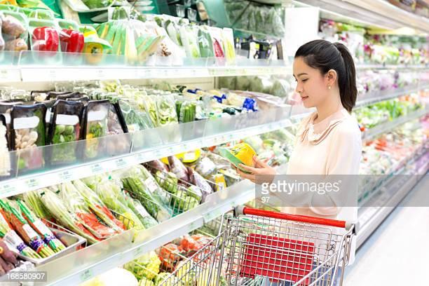 La femme attentivement de l'avis de légumes dans le magasin