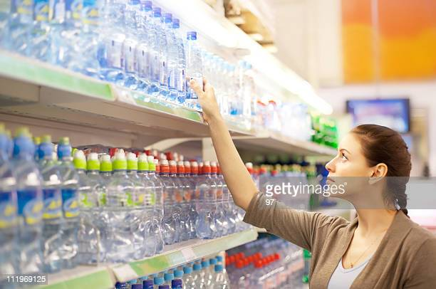 The woman buys a water bottle in shop (DOF)