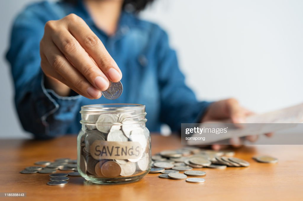 The woman hand is putting a coin in a glass  bottle and a pile of coins on a brown wooden table,Investment business, retirement, finance and saving money for future concept. : Stock Photo