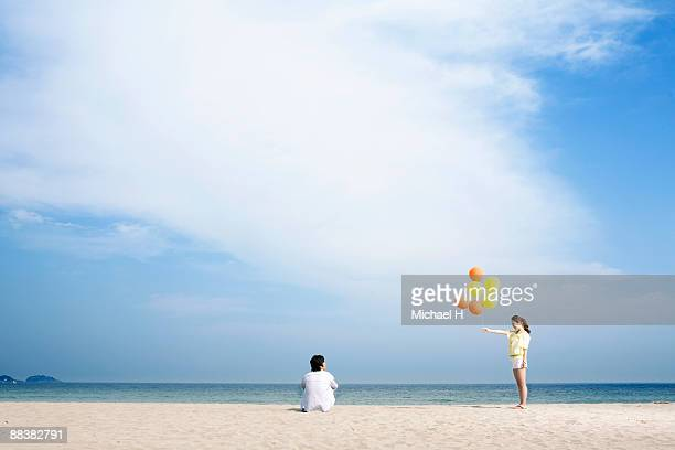 The woman hands the man the balloon on the beach.