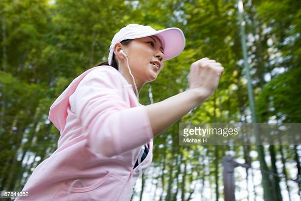 The woman is running in the Bamboo forest.