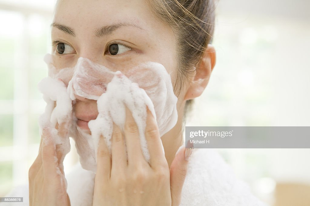 The woman is washing her face.  : Stock Photo