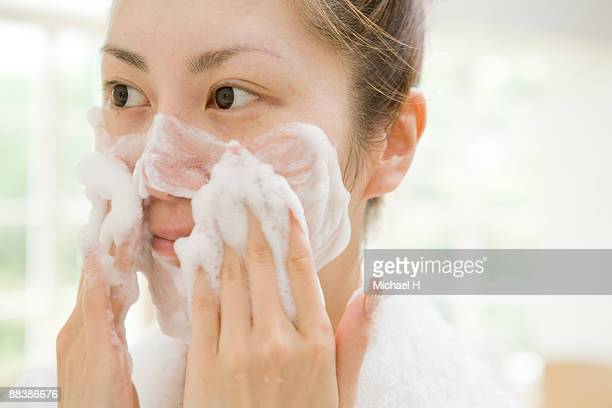 The woman is washing her face.