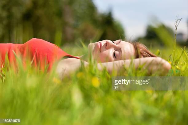 Die Frau liegt auf dem Gras.