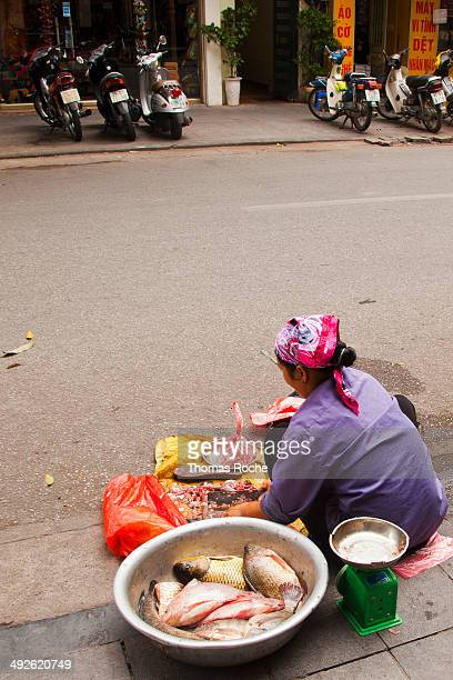 The woman runs a sidewalk restaurant and does the food cleaning in the local street.