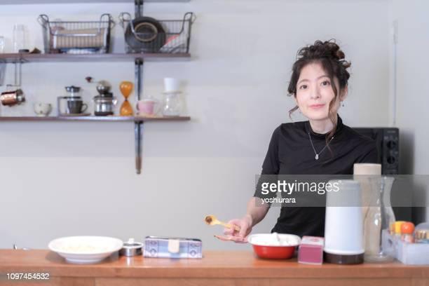 女性は、笑顔のキッチンに立っています。 - 専業主婦 ストックフォトと画像