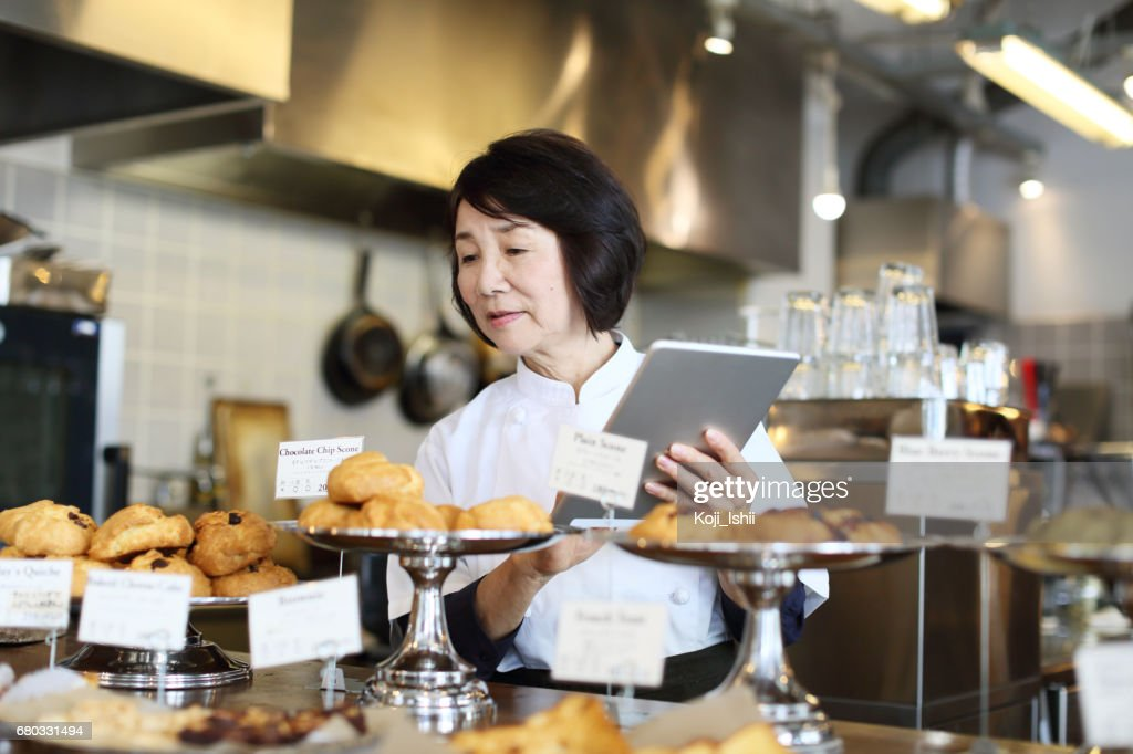 The woman storekeeper who manages the product with a tablet : Stock Photo