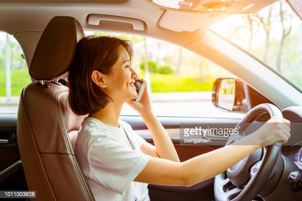 The woman using smart phone in the car