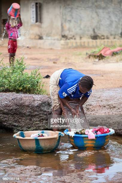 the woman washes in a street stream, in kenema, sierra leone, just after the rainy season - sierra leone stock pictures, royalty-free photos & images