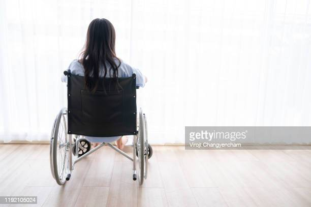 the woman who sat on the wheelchair looked away from the window of the hospital - 麻痺 ストックフォトと画像