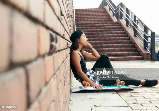 the woman who sits down near skateboarding - yusuke nishizawa fotografías e imágenes de stock