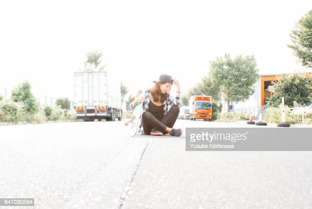 the woman who sits down near skateboarding - yusuke nishizawa stock-fotos und bilder