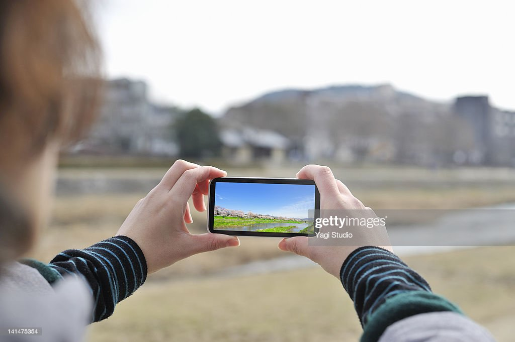 The woman who takes a picture with a smart phone : Foto de stock