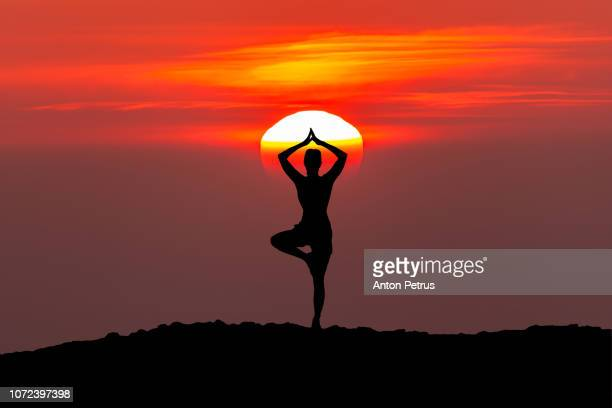 The woman with yoga posture at sunset.