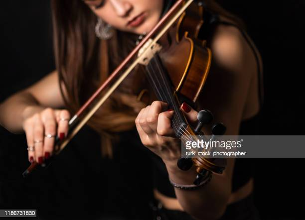 the woman's hand on the strings of a violin - classical musician stock pictures, royalty-free photos & images