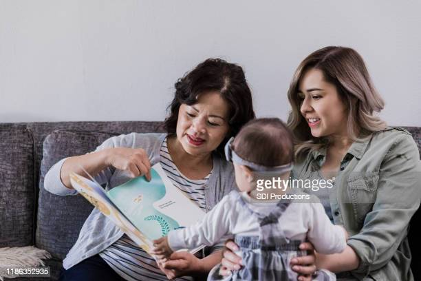 the women and the baby look at the picture book - mother in law stock pictures, royalty-free photos & images