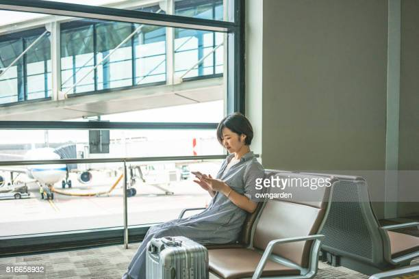 The women looking at smartphone at airport while waiting for flight