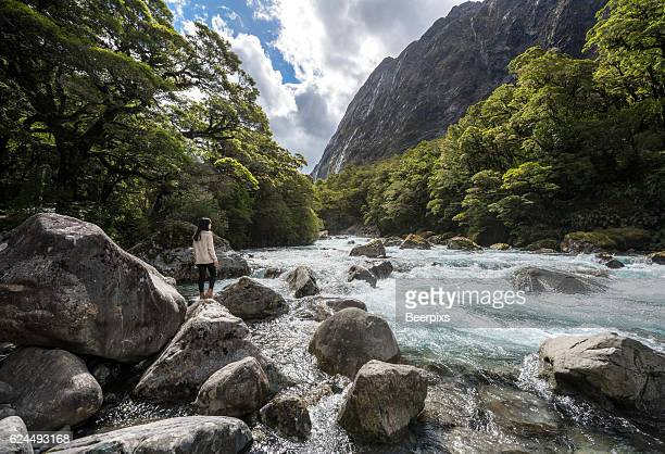 the women stands on a stone in the midst of watercourse with mountains in milford highway. - uncultivated stock pictures, royalty-free photos & images