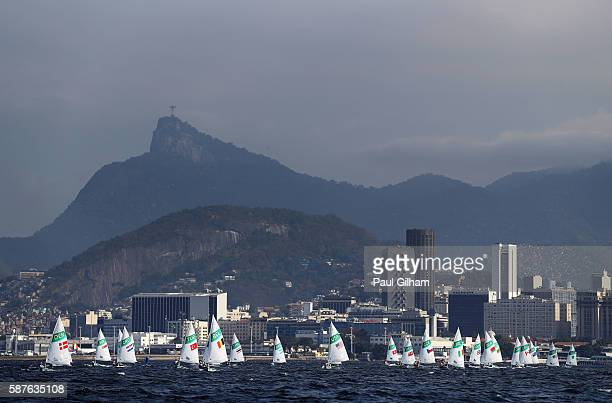 The Women's Laser Radial class competes with Christ the Redeemer in the background on Day 4 of the Rio 2016 Olympic Games at the Marina da Gloria on...