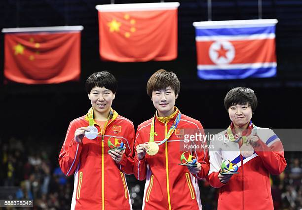 The women's table tennis singles gold medalist Ding Ning of China silver medalist Li Xiaoxia of China and bronze medalist Kim Song I of North Korea...