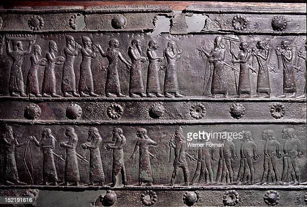 The wooden gates of Shalmaneser III with bands of relief decoration in bronze The top detail shows the king receiving tribute of the Phoenician city...