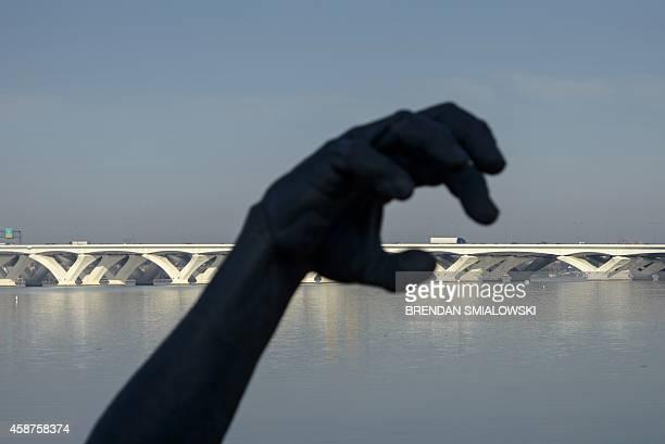 "The Woodrow Wilson Memorial Bridge is seen behind part of the 'Awakening"" sculpture November 10, 2014 in National Harbor, Maryland. AFP PHOTO/Brendan..."