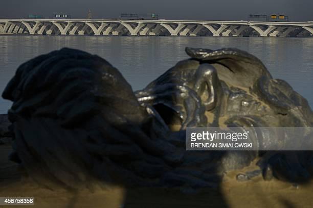 "The Woodrow Wilson Memorial Bridge is seen behind the 'Awakening"" sculpture November 10, 2014 in National Harbor, Maryland. AFP PHOTO/Brendan..."