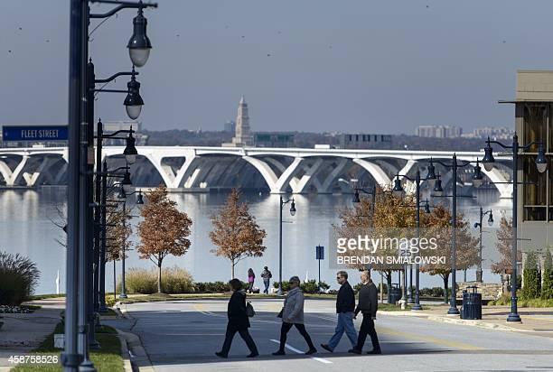 The Woodrow Wilson Memorial Bridge is seen in the background as people walk around National Harbor November 10, 2014 in Maryland.AFP PHOTO/Brendan...