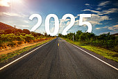 The word 2025 behind the tree of empty asphalt road at golden sunset and beautiful blue sky.