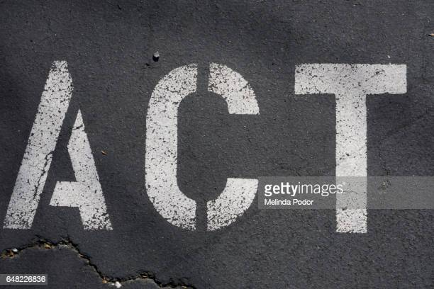 "the word ""act"" painted on asphalt"