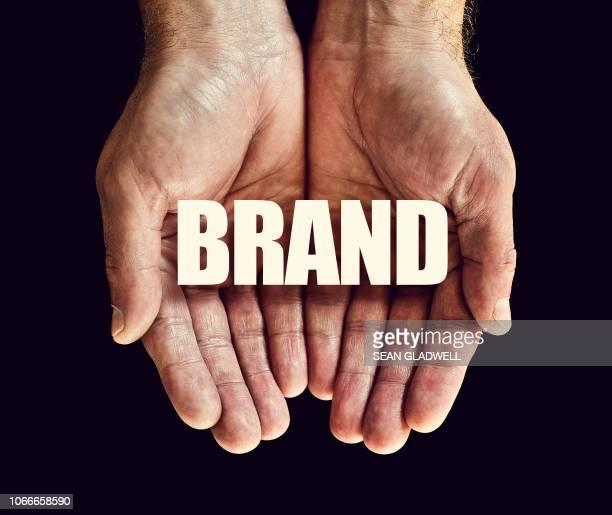 the word brand in hands - werbung stock-fotos und bilder