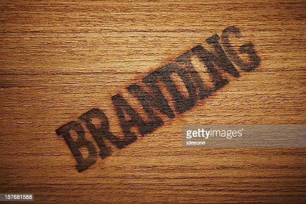 The word branding stamped diagonally on a wooden background