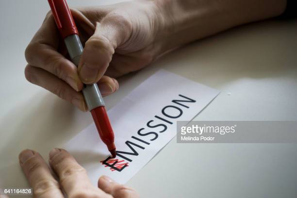 The word EMISSION, with the E crossed out to spell MISSION