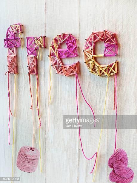 the word 'free' sewn on a wall with yarn - gratis - fotografias e filmes do acervo