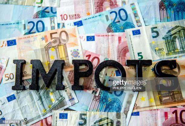 The word 'Impots' is seen on top of euro banknotes in Lille on August 25 2014 AFP PHOTO/PHILIPPE HUGUEN