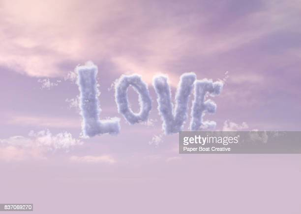 the word love arranged with clouds to look like a word up in the air with lilac or plum colored sky - typographies stock photos and pictures