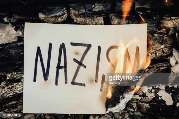 the word nazism on white paper burning in a flame of fire - nazi swastika stock pictures, royalty-free photos & images
