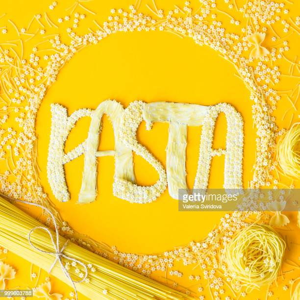 The word pasta is laid out in voluminous letters from small raw macaroni in a circle among...