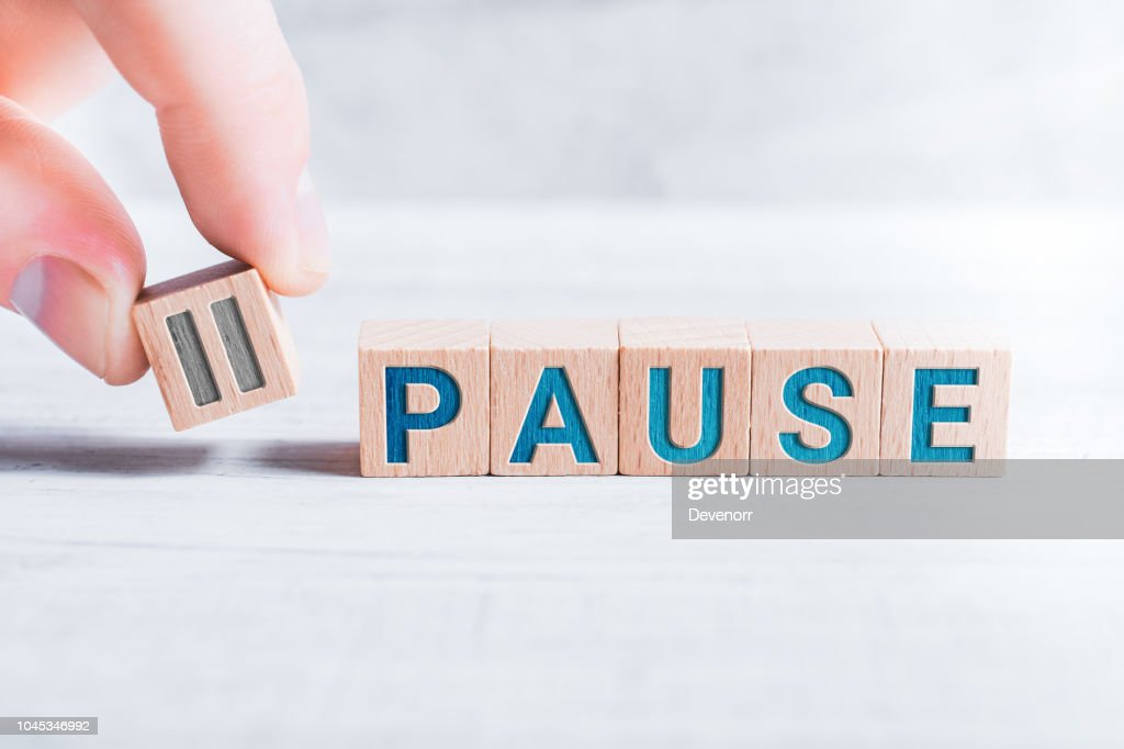 The Word Pause Formed By Wooden Blocks And Arranged By Male Fingers On A White Table : Stock Photo