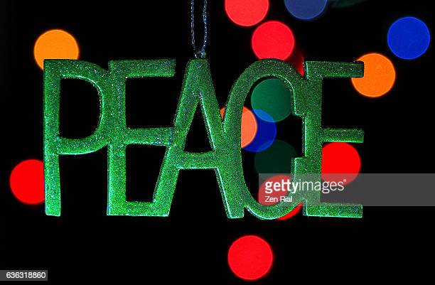 The word Peace hangs as a Christmas ornament against multicolored defocused lights on black background