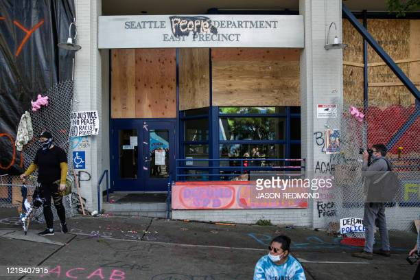 """The word """"people"""" is spray painted over the word """"police"""" on the closed Seattle Police Department's East Precinct now surrounded by the area known as..."""