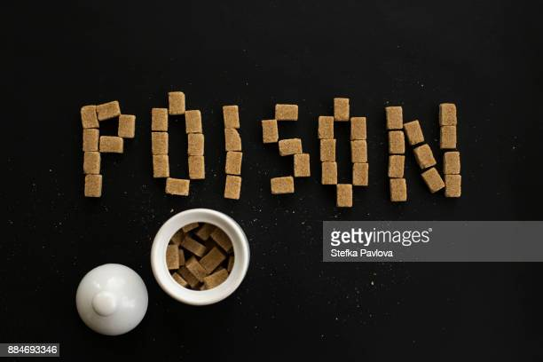 the word poison written with sugar cubes on black background - sugar bowl crockery stock photos and pictures