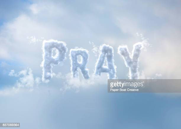 the word pray formed with a cloudy font with the heaven and the blue sky behind it - typographies stock photos and pictures