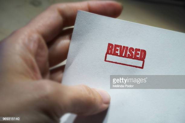 The word REVISED stamped on a piece of paper